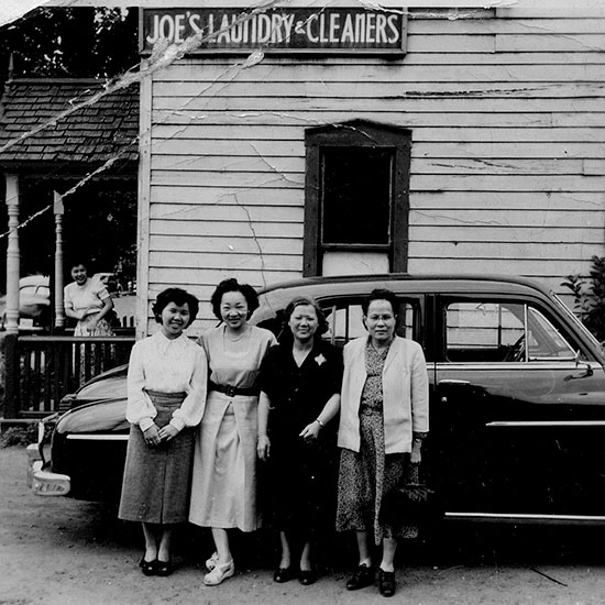 In front of Shung Joe's laundry, Slater Street, Ottawa, circa. late 1950s<br />L to R: Betty Joe, Margaret (née Joe) Hamilton, Mrs. Shung Joe, Unknown. (Courtesy of William Joe)